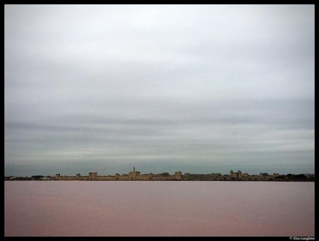 L'eau rose des marais salants camarguais et les remparts d'Aigues-Mortes. © Elsa Lunghini